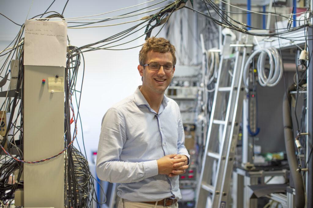 Portrait de Gautier Depambour devant des cables du Laboratoire Kastler-Brossel.