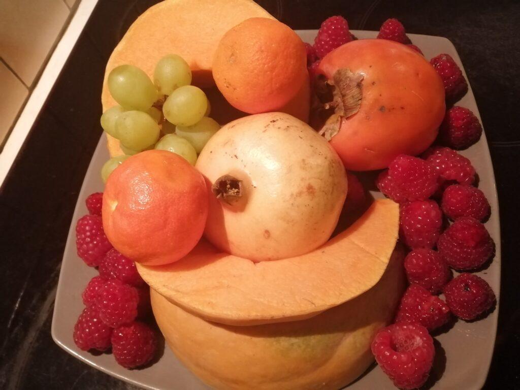 Sur une assiette sont disposés une grenade, un kaki, des clémentines, du raison, des framboises et de la papaye.