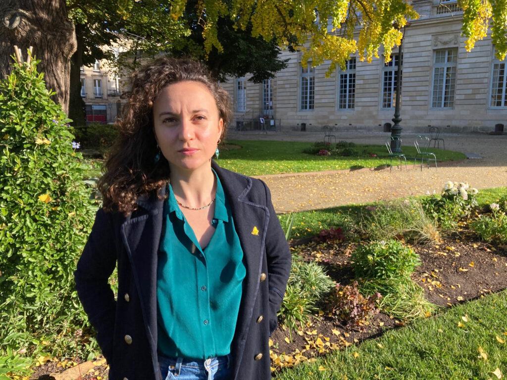 Morgane Robert est une jeune femme aux cheveux bruns et bouclés, elle se trouve dans un jardin ensoleillé. A l'arrière plan on voit aussi un bâtiment et des chaises.