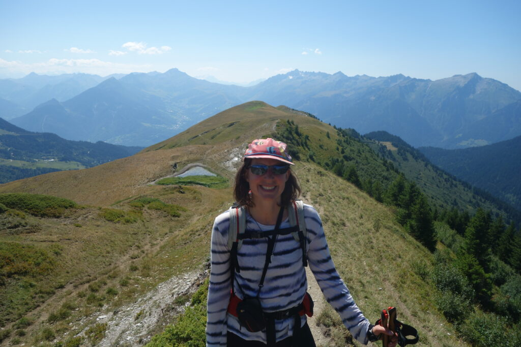 La chercheuse est en pleine randonnée, sous le soleil, caquette et lunettes de soleil. Derrière elle, de belles montagnes et quelques points d'eau.