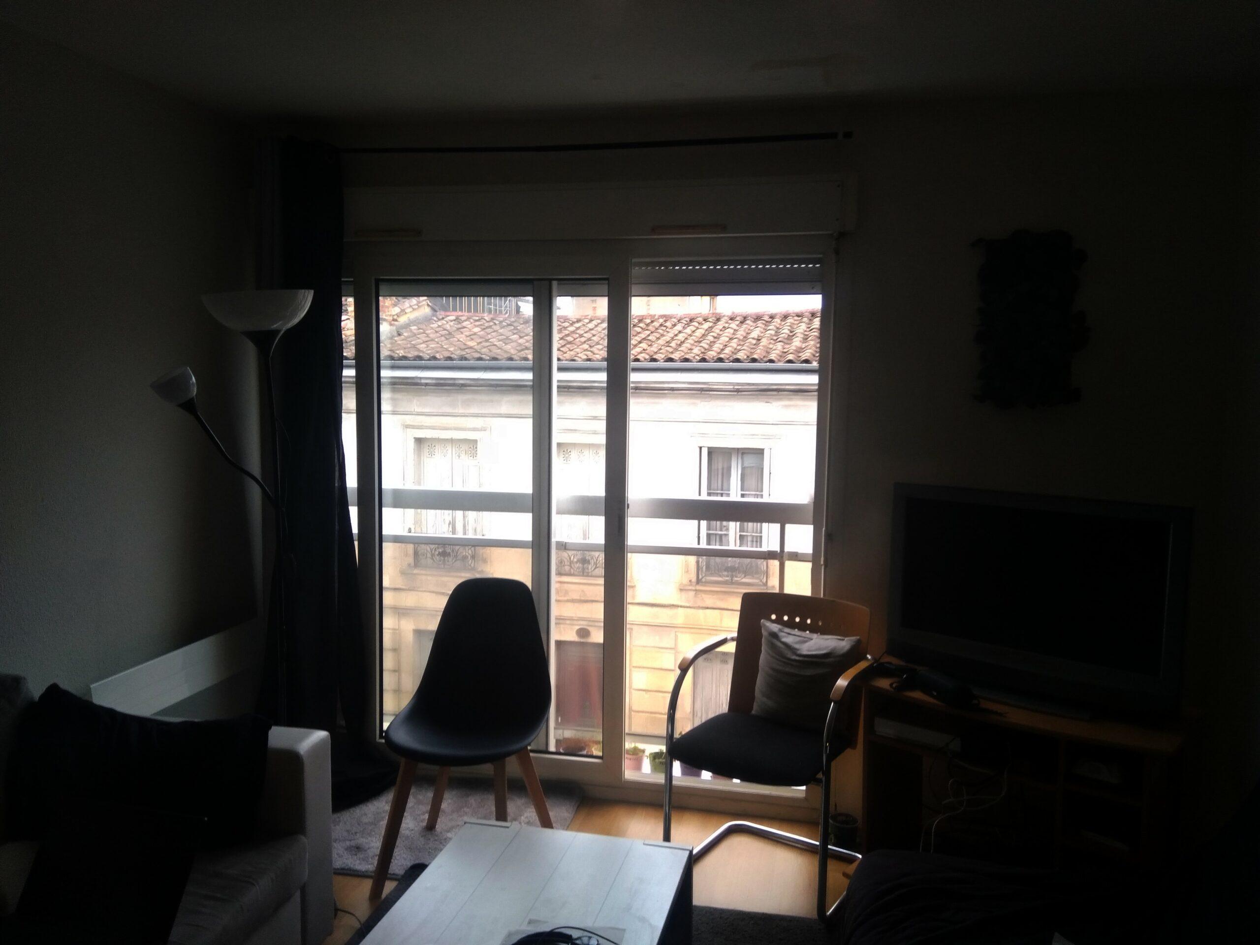 Photo d'un appartement. Seule une porte-fenêtre permet d'apporter de la lumière. L'ambiance est sombre, l'autre côté de la rue est visible.
