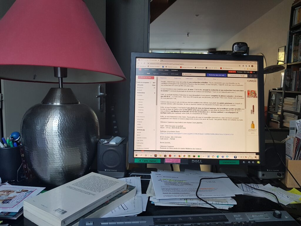 L'ordinateur et les nombreux papiers et livres prennent toute la place sur le petit bureau. On voit aussi une petite enceinte et une grande lampe à l'abat-jour rose.