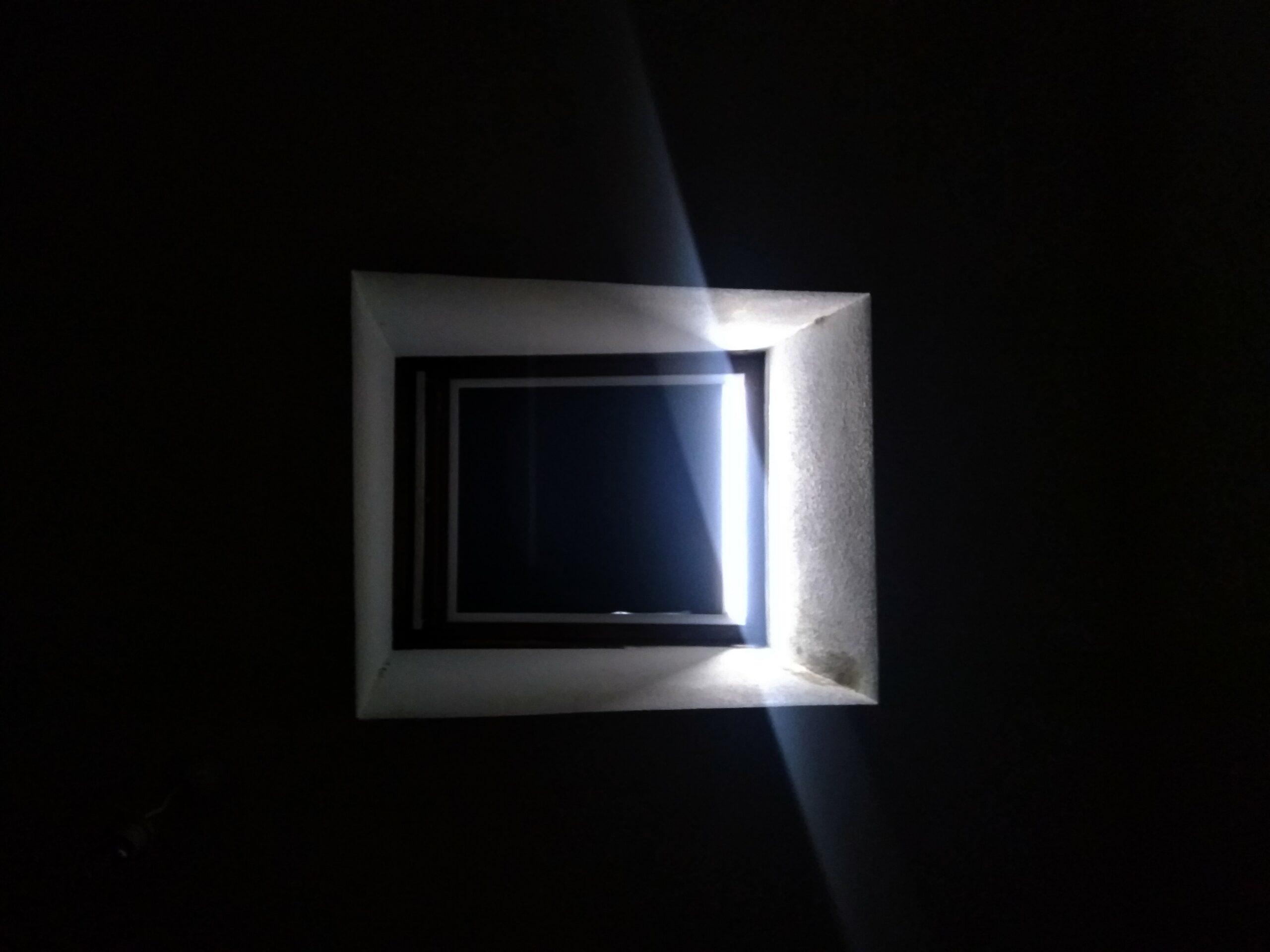 Photo d'un Velux®, fermé, vu d'en-dessous. Seul un rayon de lumière réussit à passer à travers.