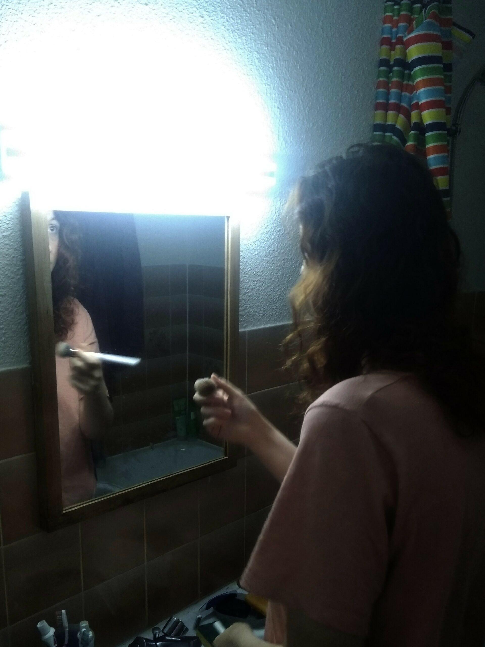 Photo d'Aurore Valex se maquillant sous un néon blafard.