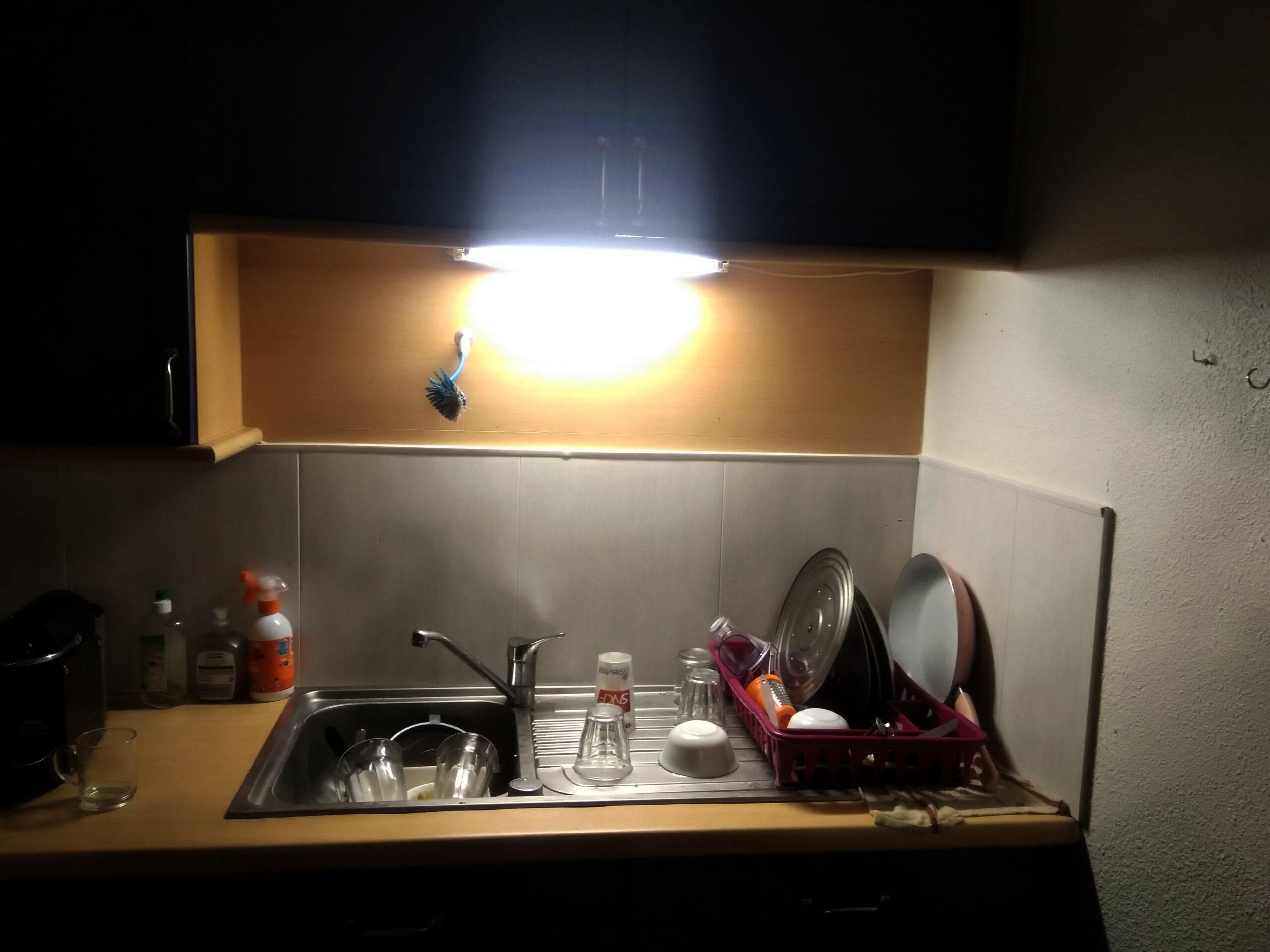 Photo d'un évier rempli de vaisselle et éclairé uniquement par un néon.