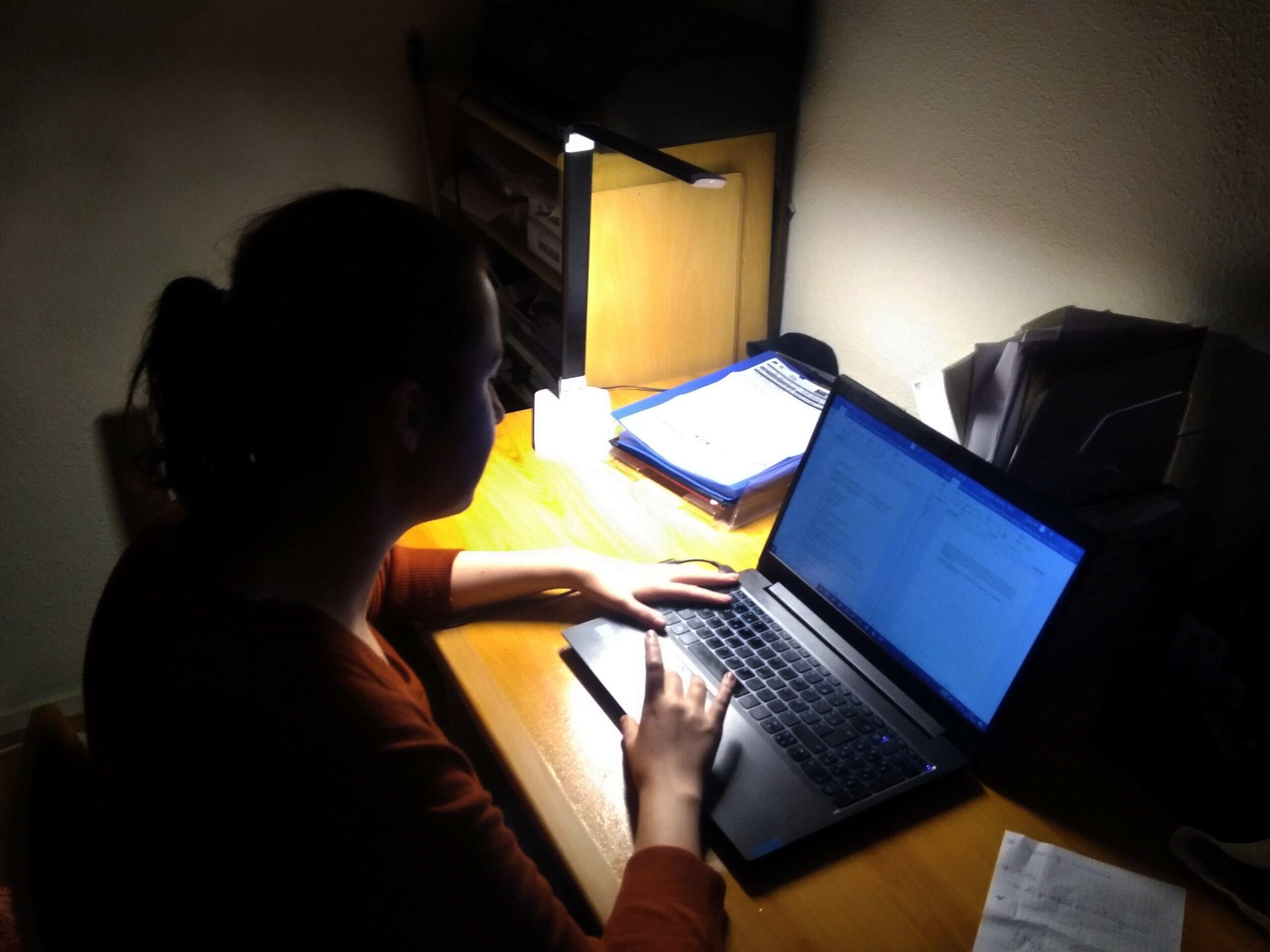 Photo d'Aurore travaillant calfeutrée dans le noir et éclairée uniquement par son écran d'ordinateur et une lampe de bureau dérisoire.