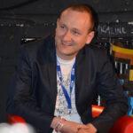 Sébastien Genvo, un homme à la coupe de cheveu rasé, il est sur un fauteuil en train de sourire. Il possède un T-shirt avec par-dessus un costume et un tour de cou bleu.