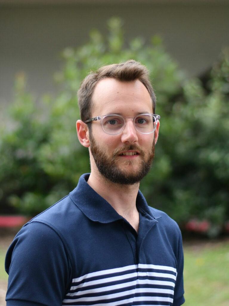 Portrait de Matthieu Guemann en plan poitrine. Il pose souriant et le regard fixé à la caméra devant un fond naturel et boisé. Il a les cheveux châtains clairs, une barbe courte de la même couleur que ses cheveux et des lunettes transparentes. Il porte un polo rayé bleu et blanc.