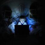 Dans le noir, un petit garçon en bas âge est assis entre ses parents dans leur lit. Il y a très peu de lumière mais le petit garçon a le visage éclairé par la lumière de son ordinateur portable qu'il regarde très attentivement. Il est tellement concentré qu'il en garde la bouche entrouverte.
