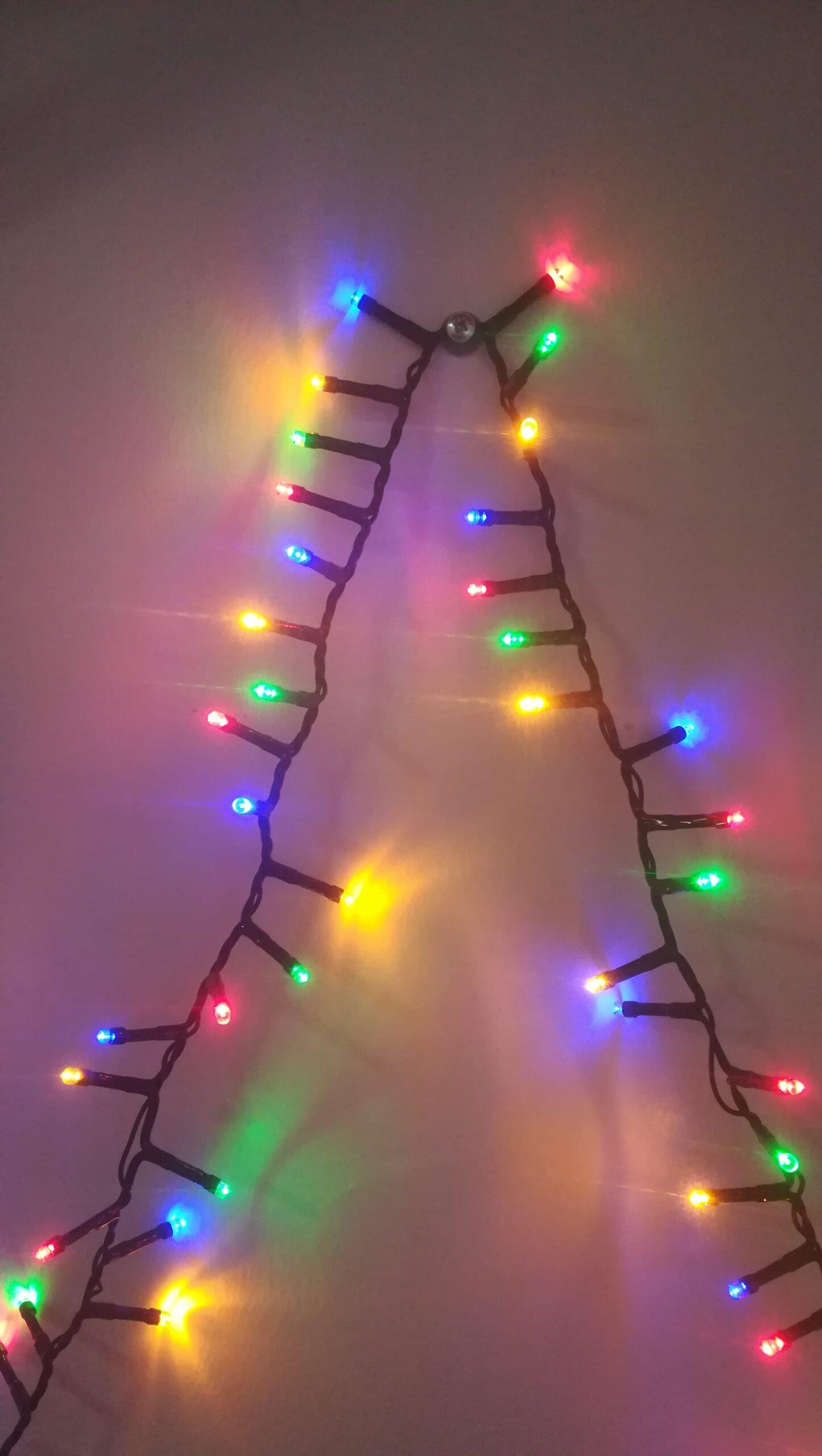 L'image est centrée sur la guirlande lumineuse. Dans la première partie, à gauche, elle grimpe le long d'un mur nu qui reflète ses couleurs bleues, rouges, jaunes et vertes. Jusqu'à un clou enfoncé dans le mur sur lequel elle se repose avant de redescendre, symétrie axiale presque parfaite.