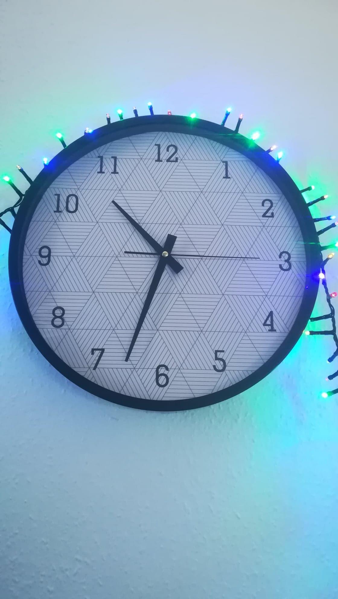 L'image est centrée sur une horloge murale affichant dix heure trente-trois. La trotteuse est arrêtée sur un quart de minutes. Au-dessus de cette horloge se promène la guirlande lumineuse, qui affiche des lueurs froides bleues et vertes. Le mur est nu, blanc.