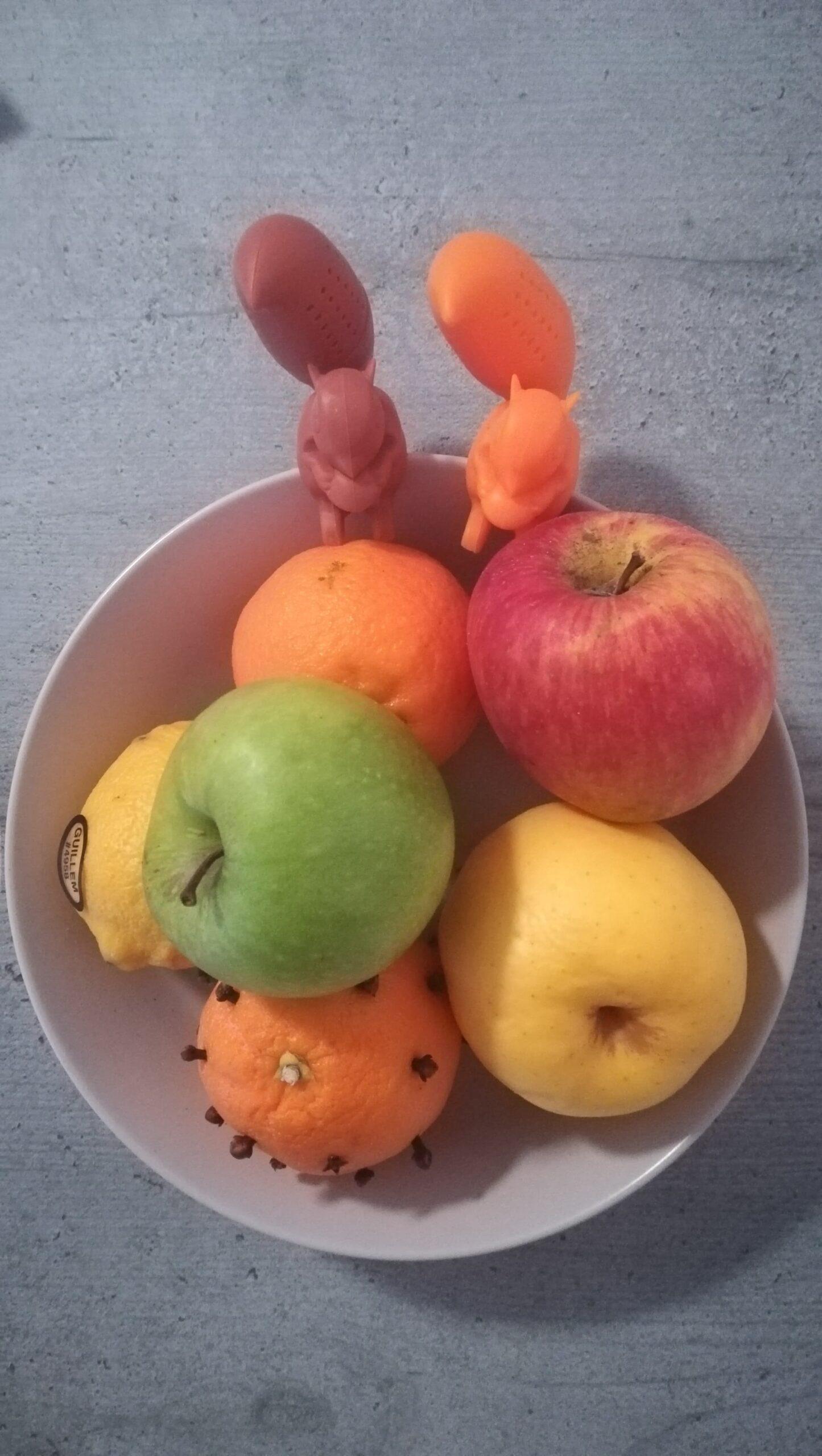 Sur une table grise, un plateau de fruits est photographié d'en haut. Celui-ci contient trois pommes : une rouge, une jaune et une verte, au-dessus. Un citron, sur la gauche, arbore une étiquette. En bas de l'image, une clémentine est percée de clous de girofles, lui conférant une apparence de hérisson. Plus haut, une autre clémentine, est lisse, elle. Sur les bords hauts du plateau, deux infuseurs à thé en forme d'écureuils sont côte à côte. Celui de gauche est marron, l'autre, à droite, orange.
