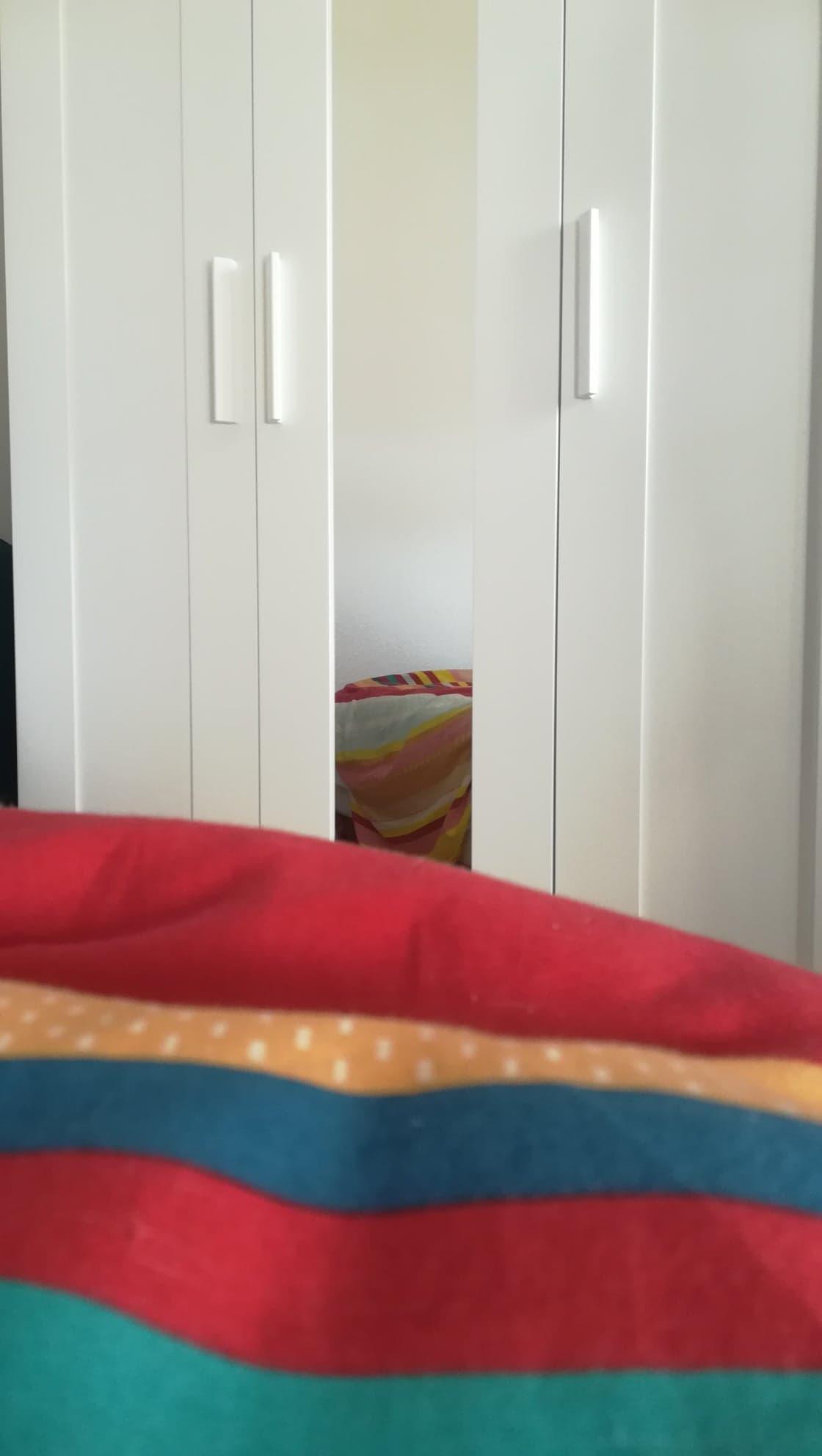 En bas de l'image, au premier plan flou, quelques bandes de couleur horizontales qui se succèdent jusqu'à un tiers de l'image environ : cyan, rouge, bleu, orange, rouge. Au second plan, une armoire blanche. À droite, une porte du meuble. Au milieu, un miroir fin et vertical reflète la couverture sur laquelle le photographe est assis. À gauche, l'autre porte du meuble, symétrique à sa sœur.
