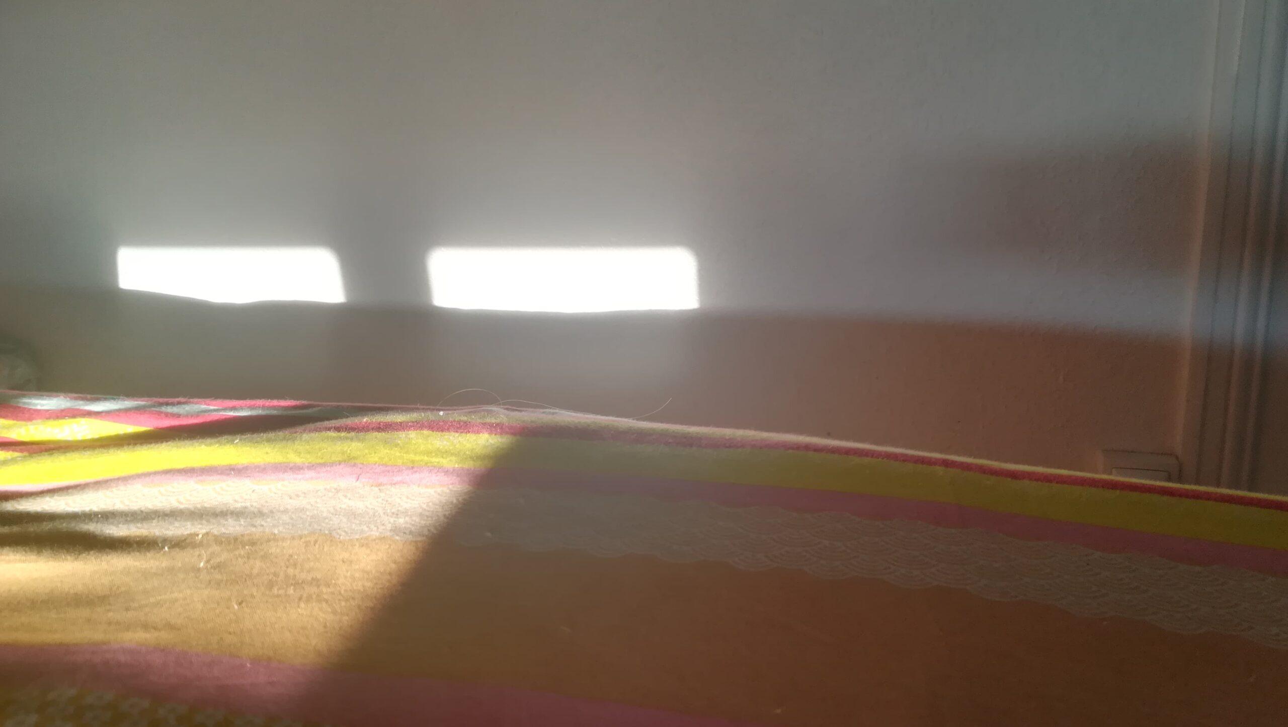 L'image est divisée en deux horizontalement. Dans la partie basse, une couverture multicolores. Le rose laisse place au orange, au blanc, au rose de nouveau que le jaune remplace, puis le rouge traversé par une bande bleue. Ces traits de couleur sont horizontaux. Au-delà de cette couverture, un mur blanc et lisse. À gauche de l'image, les rayons de soleil éclairent le lit, et forment deux tâches de lumières sur le mur, faisant penser aux yeux du soleil.