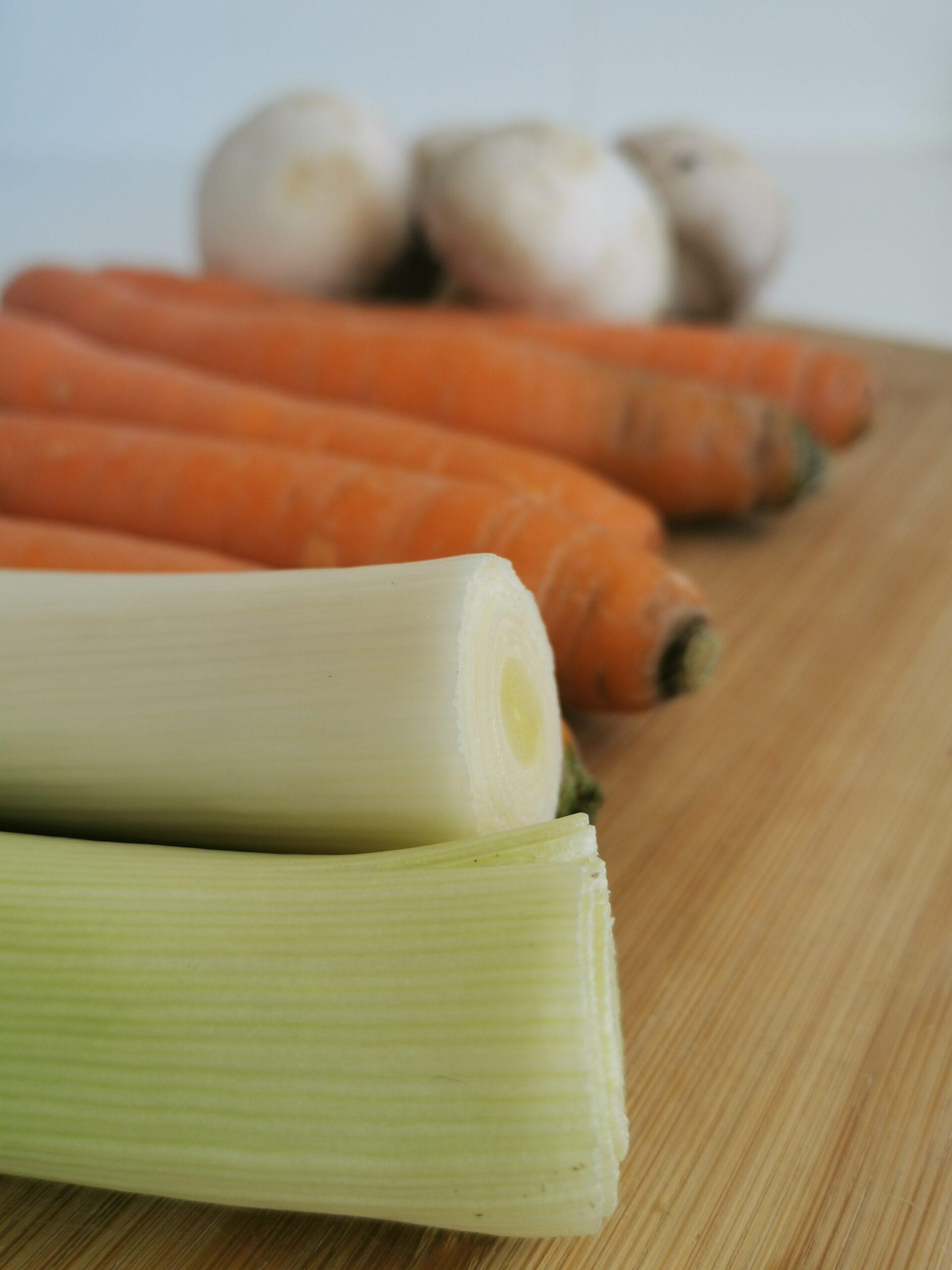 gros plan sur des légumes : poireaux, carottes et champignons en arrière plan