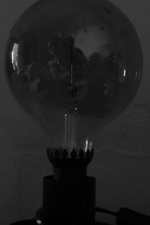 Une lampe de chevet avec une grosse ampoule éteinte, dans lequel se reflète Clémence et son appartement. L'image est en noir et blanc.