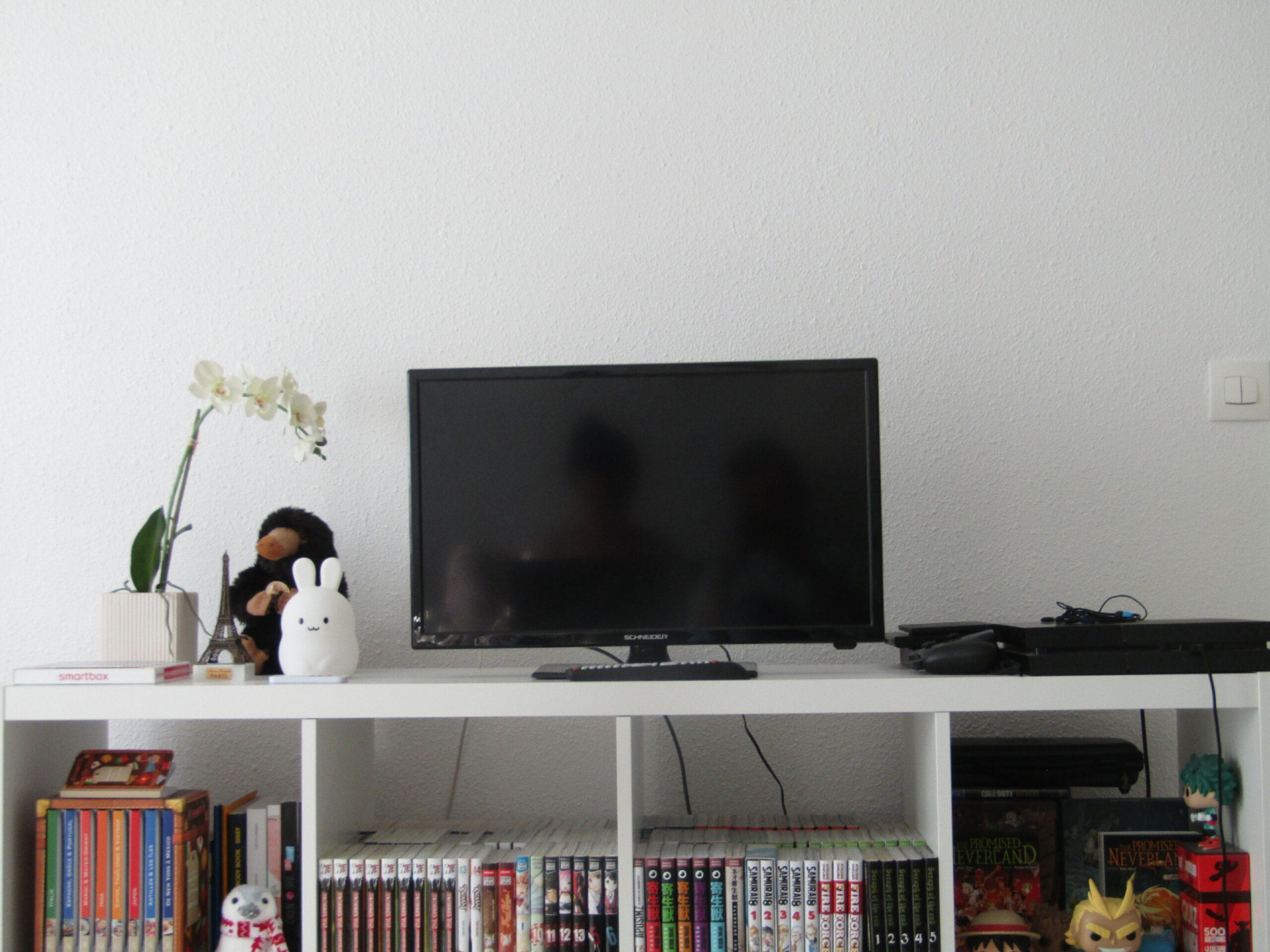 Une télé éteinte posée sur un meuble blanc.