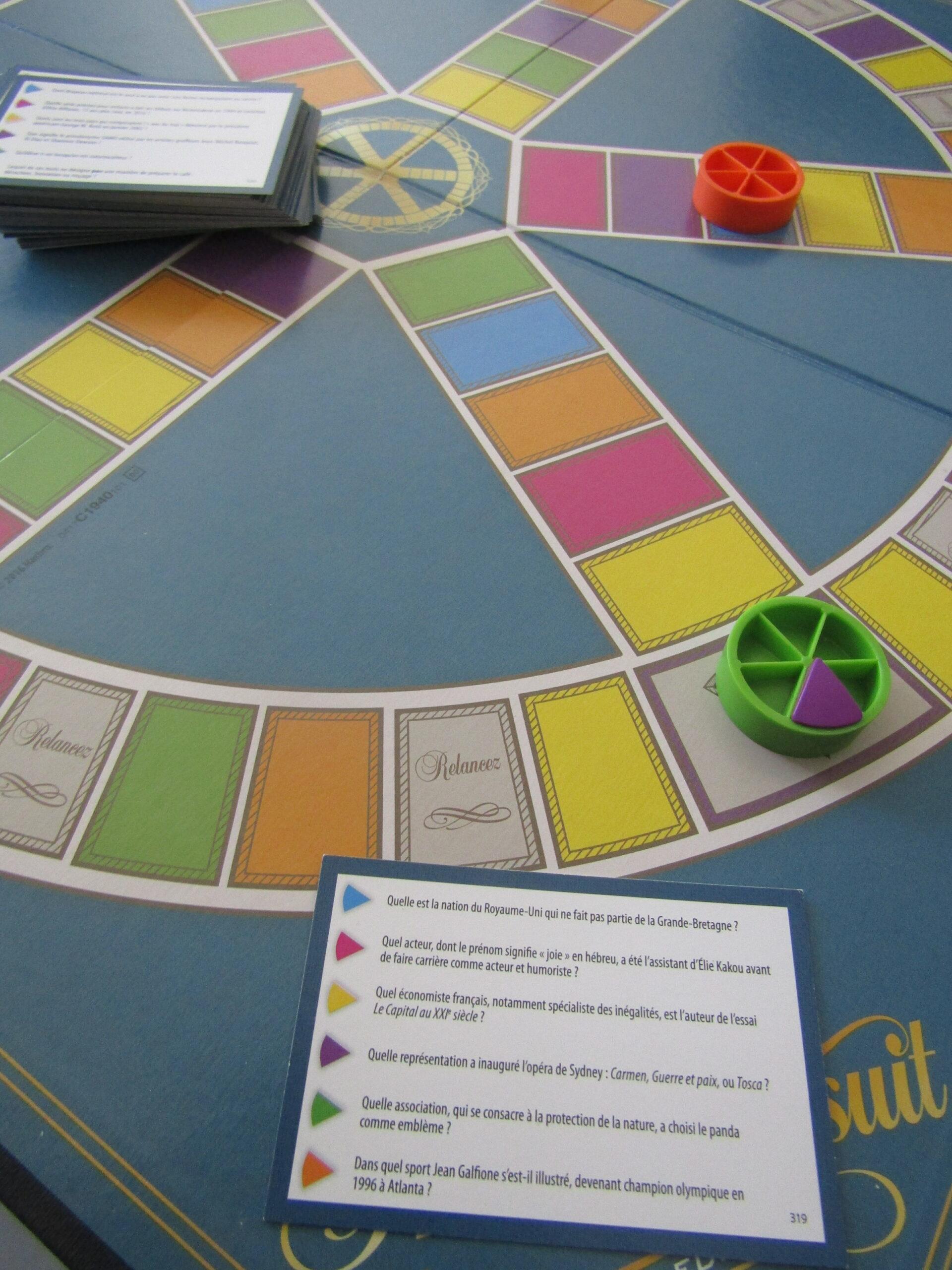 Un jeu de société Trivial Pursuit en cours de partie. On observe une carte avec des questions au premier plan suivie d'un plateau en second plan. Le plateau est composé de nombreuses cases colorées et on peut observe 2 pions sur le plateau.