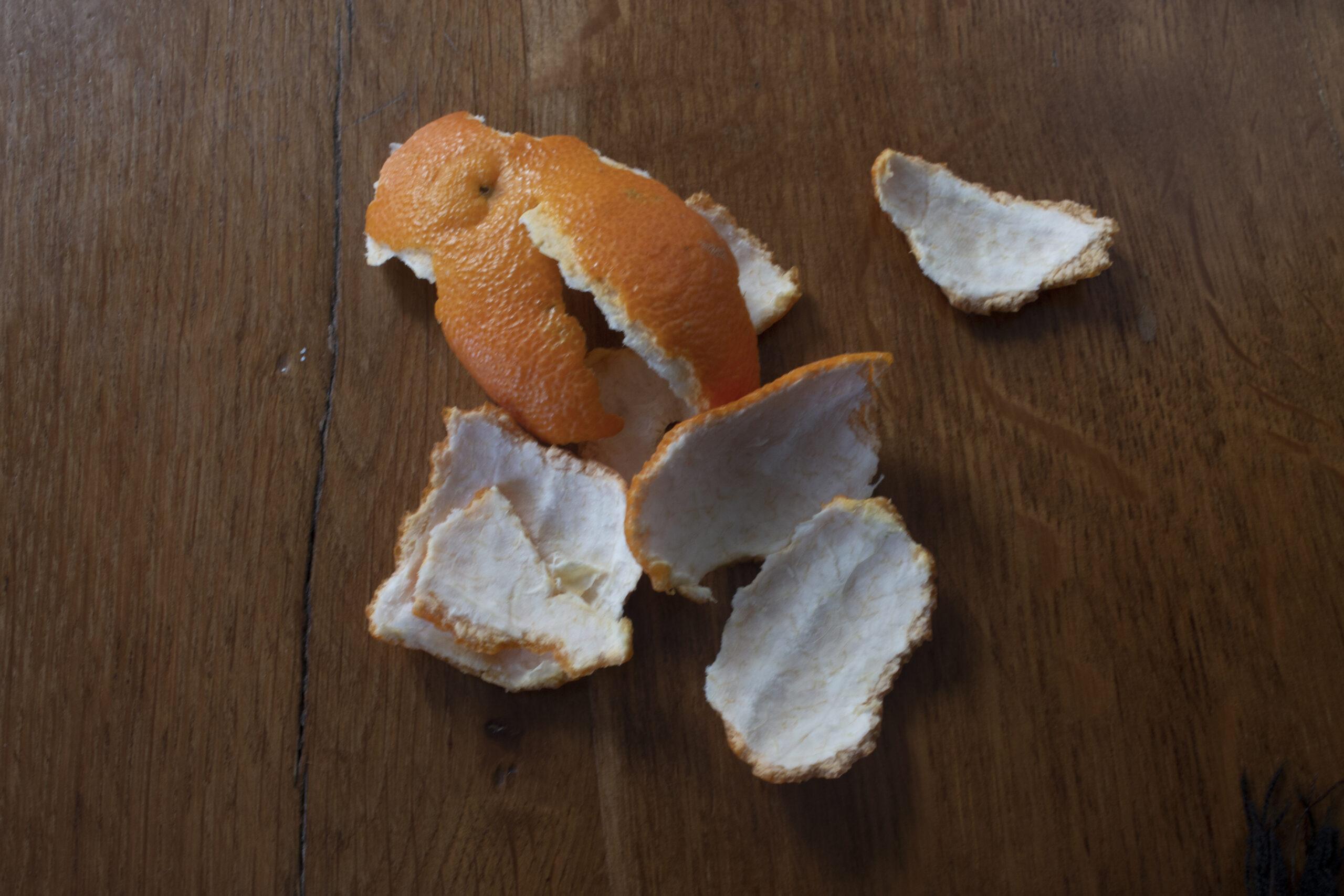 La peau orange d'une clémentine épluchée sur une table en bois.