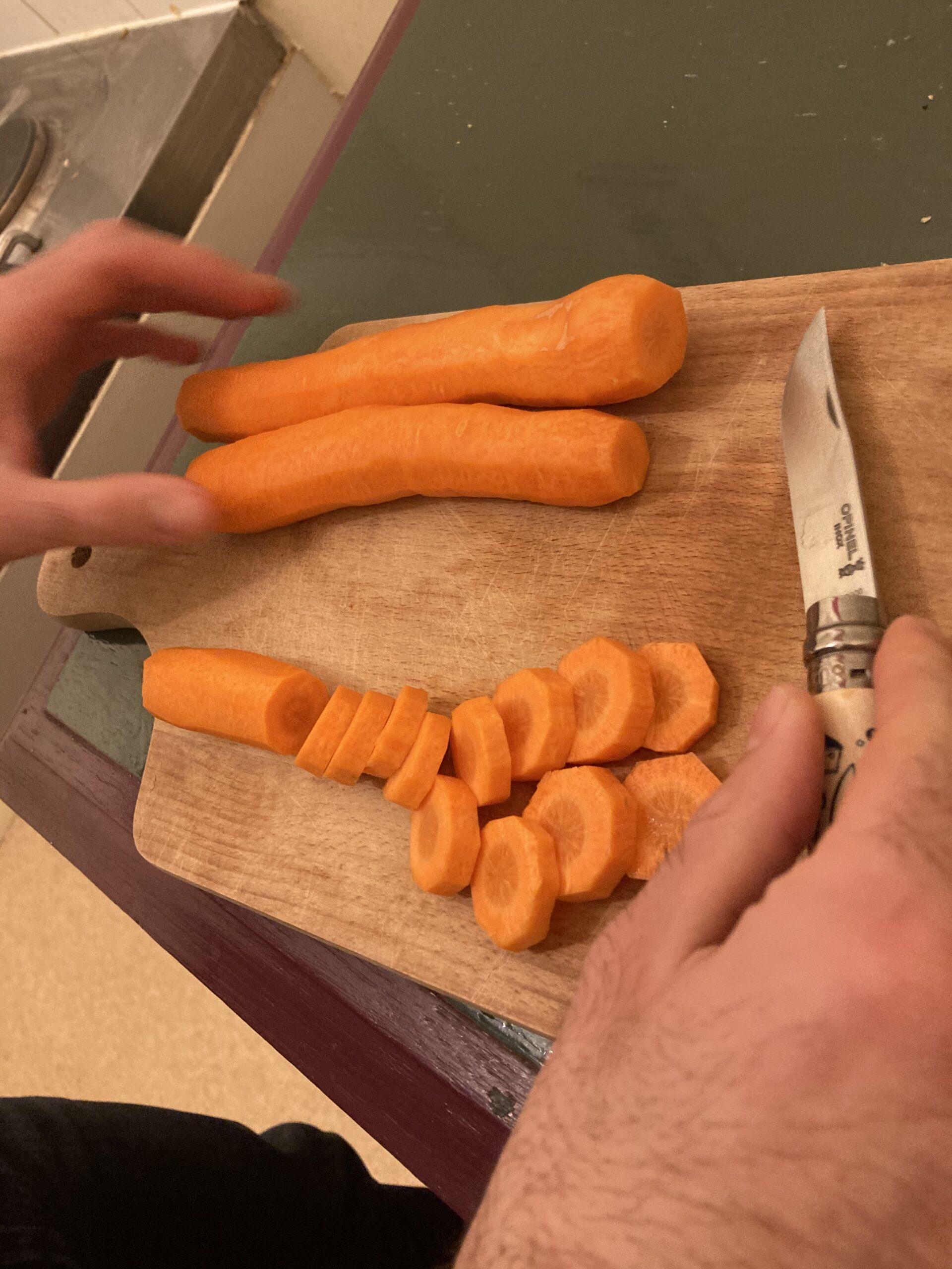 3 carottes sur une planc en train d'être découpées