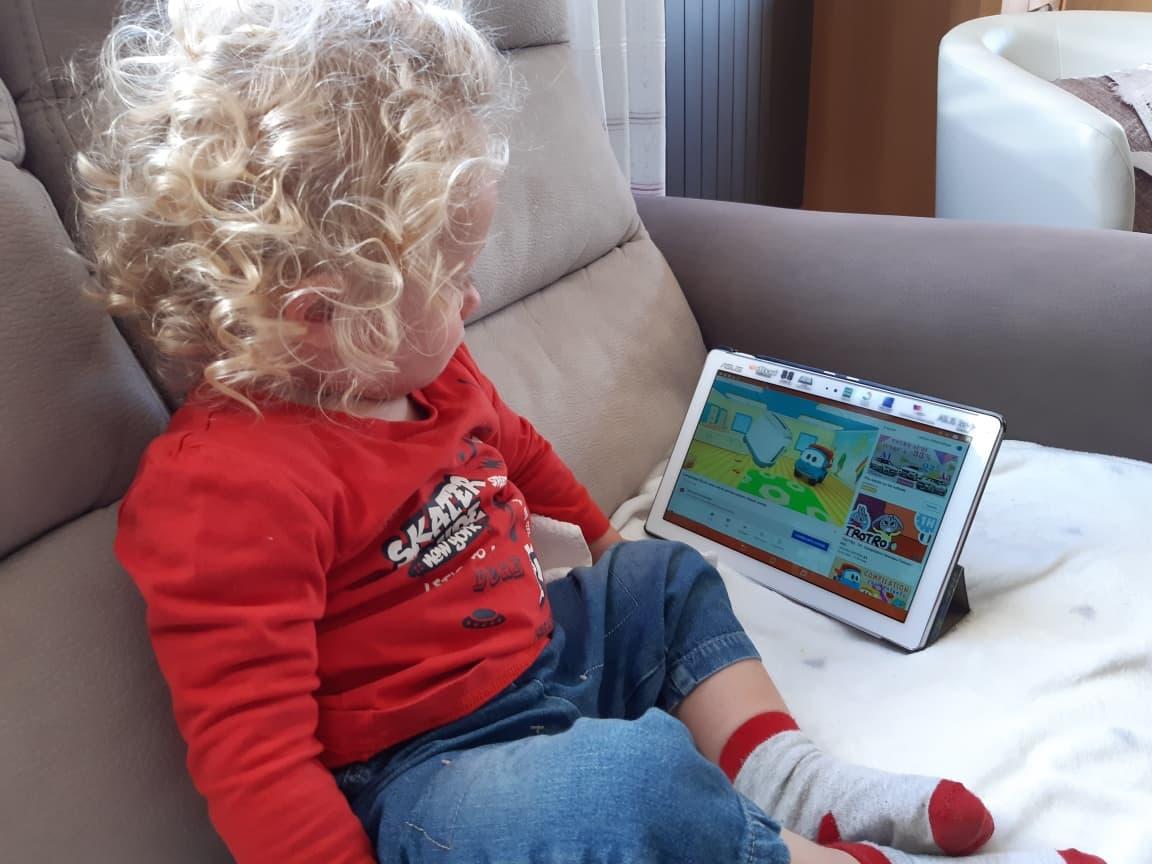 Un bébé de 18 mois, blond aux cheveux bouclés, est assis sur un canapé de couleur claire. Il regarde attentivement une animation sur Youtube.