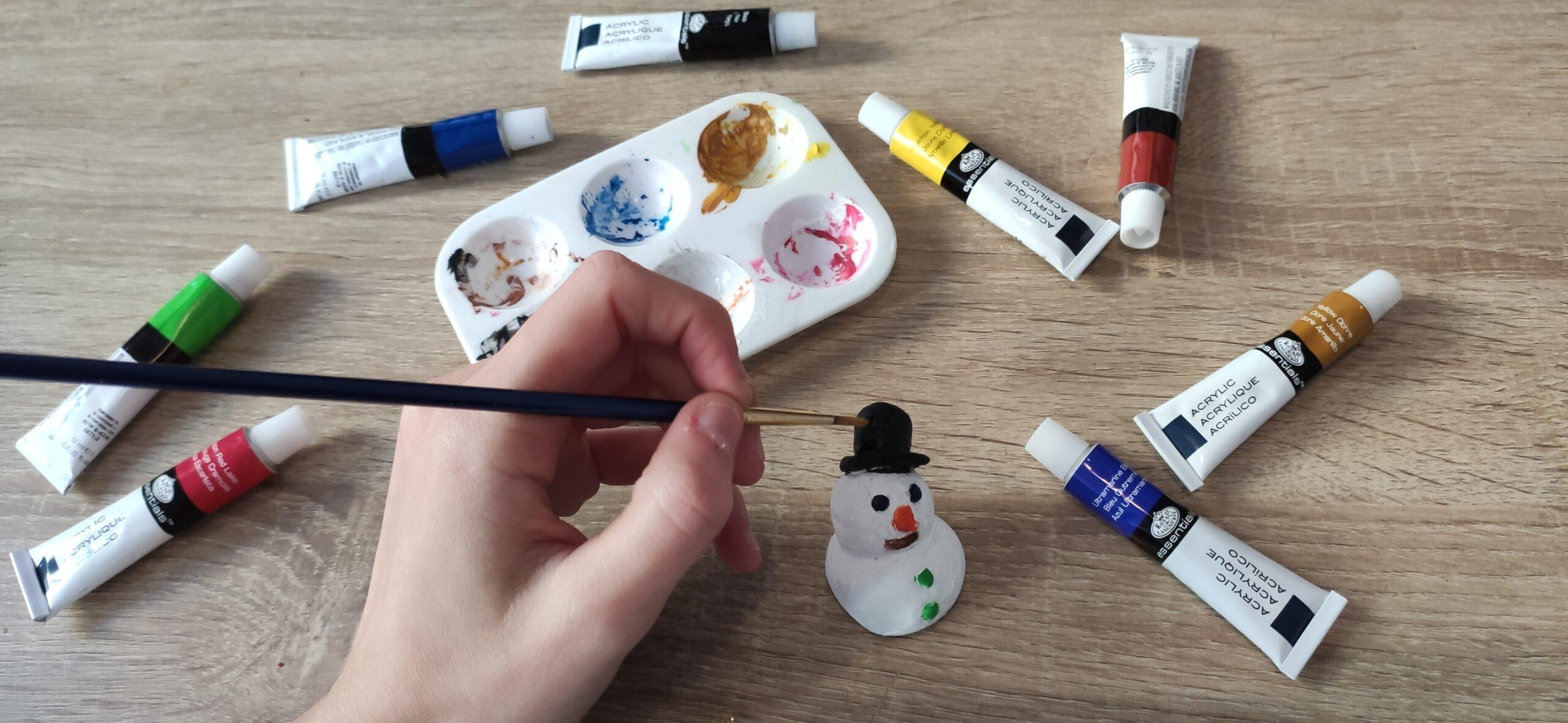Focus sur un table. Un bonhomme de neige prend des couleurs. On voit une main, tenant un pinceau bleu, peignant le chapeau du bonhomme de neige en noir. Des tubes de peinture, bleu, ocre, rouge, vert, noir et rose sont présents. Un palette pleine de peinture est visible derrière la main.