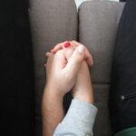 Deux mains qui se tiennent sur un canapé.