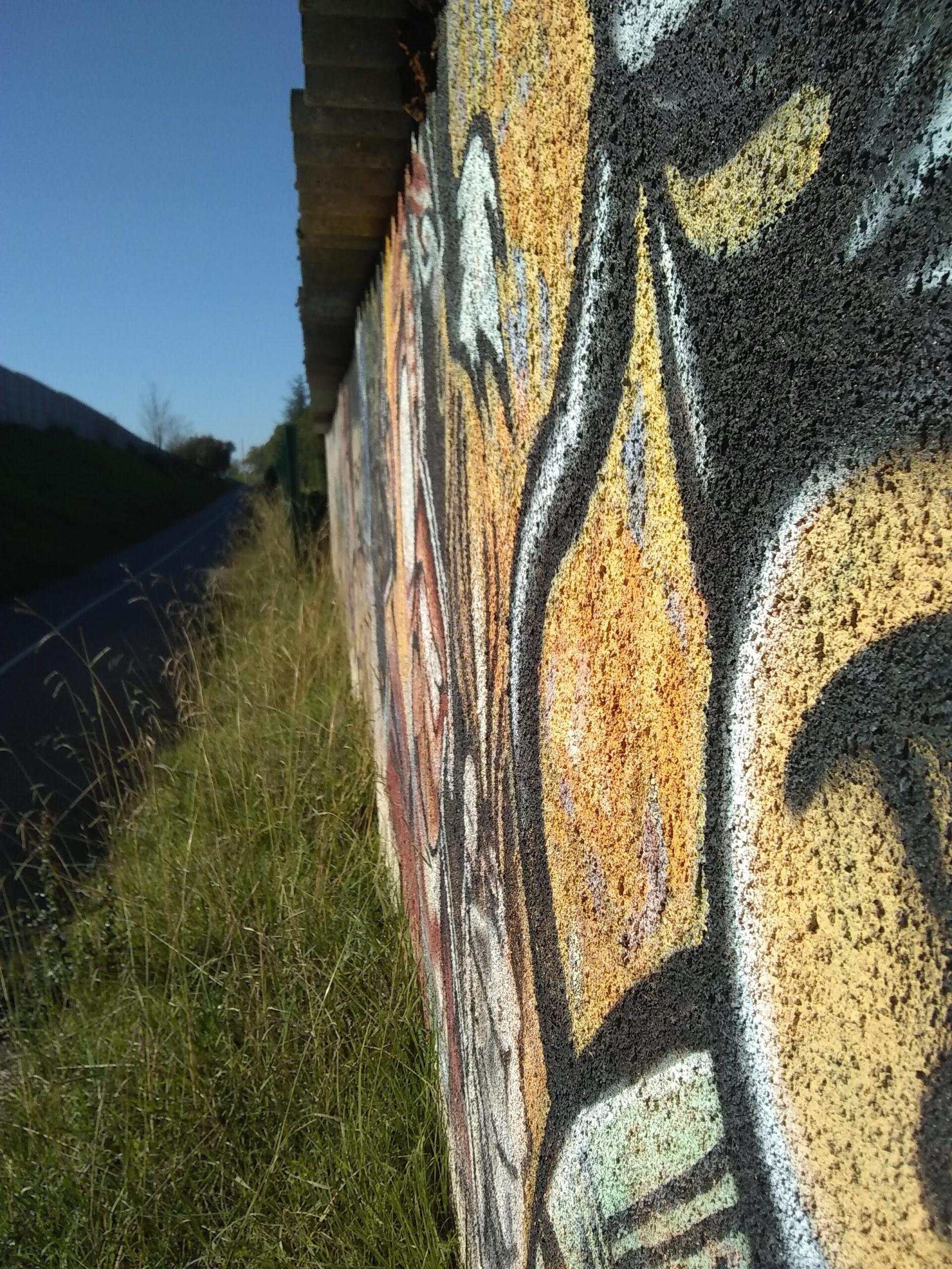 Photo prise le long d'un mur graffé. On perçoit la texture du béton, rigide, dur et sa surface pleine de petits trous.