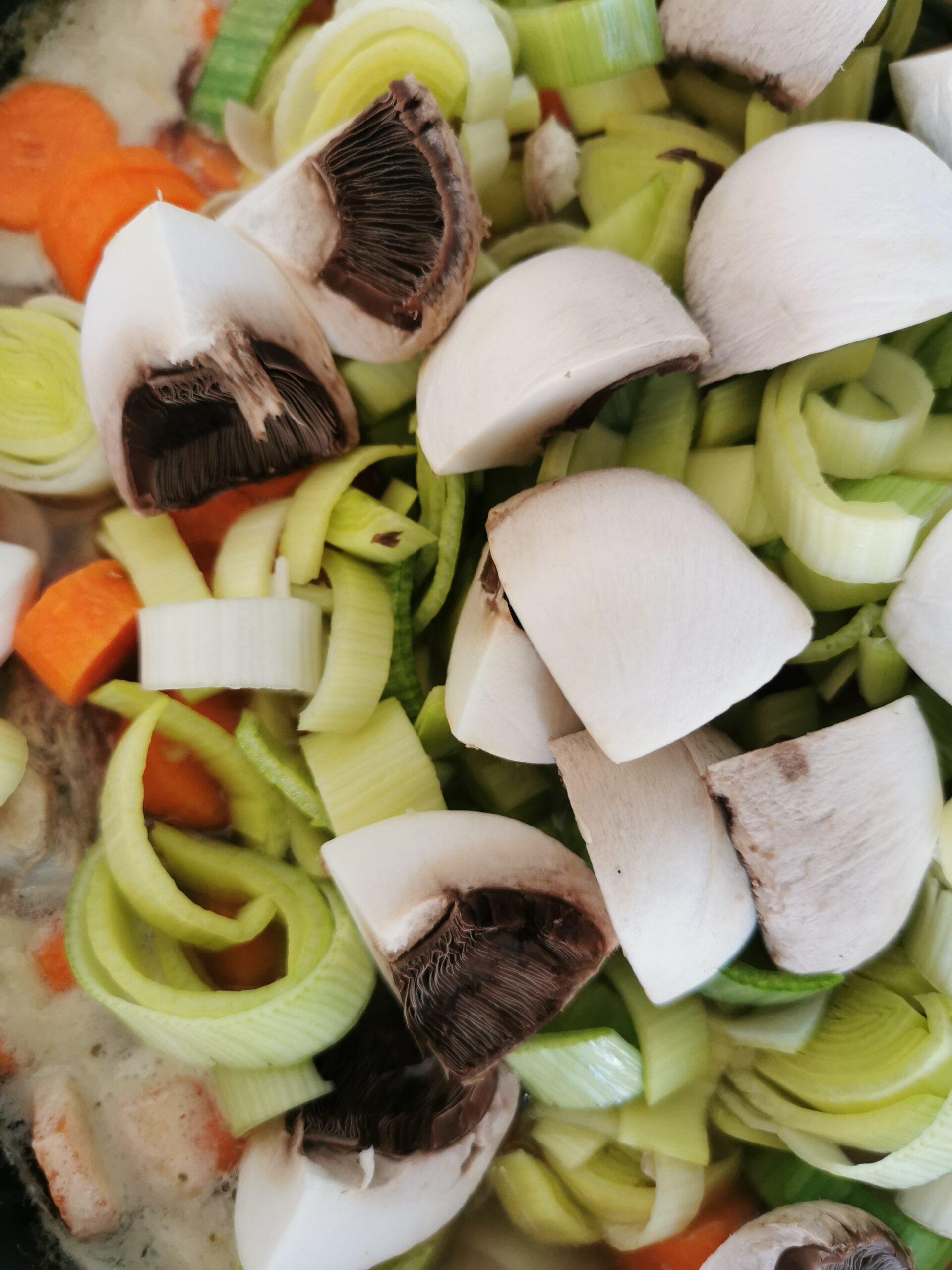 Gros plan sur des légumes coupés : champignons, poireaux et carottes