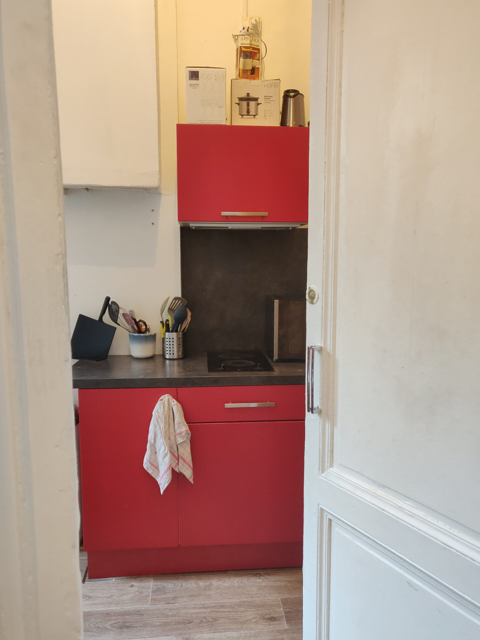Photo d'une cuisine. On voit la porte blanche entrouverte. Des meubles rouges sont visibles au centre de la photo. Un torchon est accroché sur une poignée de porte. Des ustensiles de cuisine et un micro-ondes sont visibles sur le plan de travail.