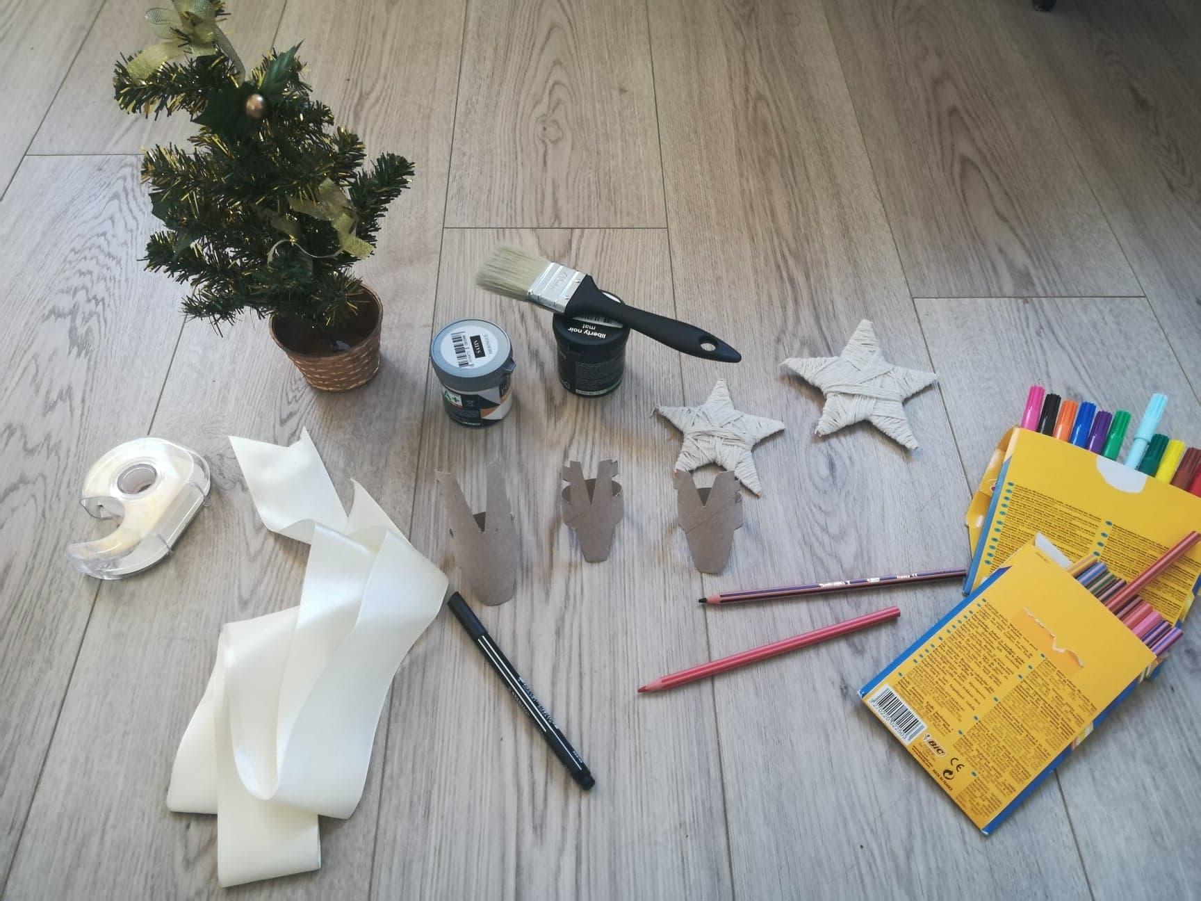 Sur le sol, du matériel est déposé. On retrouve un ruban blanc, des crayons de couleurs, des étoiles en cartons recouvertes de cordes, des rennes en carton, de la peinture, un pinceau et un petit sapin miniature.