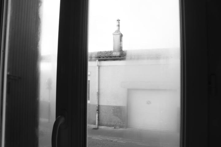 Une maison de l'autre côté de la rue prise à travers une fenêtre fermée. Il y a de la buée sur le côtés mais une trace net au milieu laisse apparaitre la cheminé de la maison d'en face. L'image est en noir et blanc.