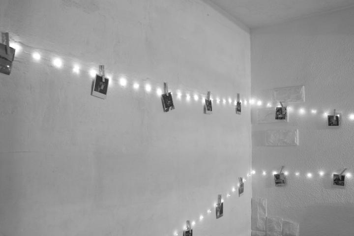 Une guirlande lumineuse accrochée au mur avec des photos épinglée avec des pinces à linge dessus. L'image est en noir et blanc.