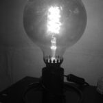 Une lampe de chevet avec une très grosse ampoule poussiéreuse est allumée. L'image est en noir et blanc.