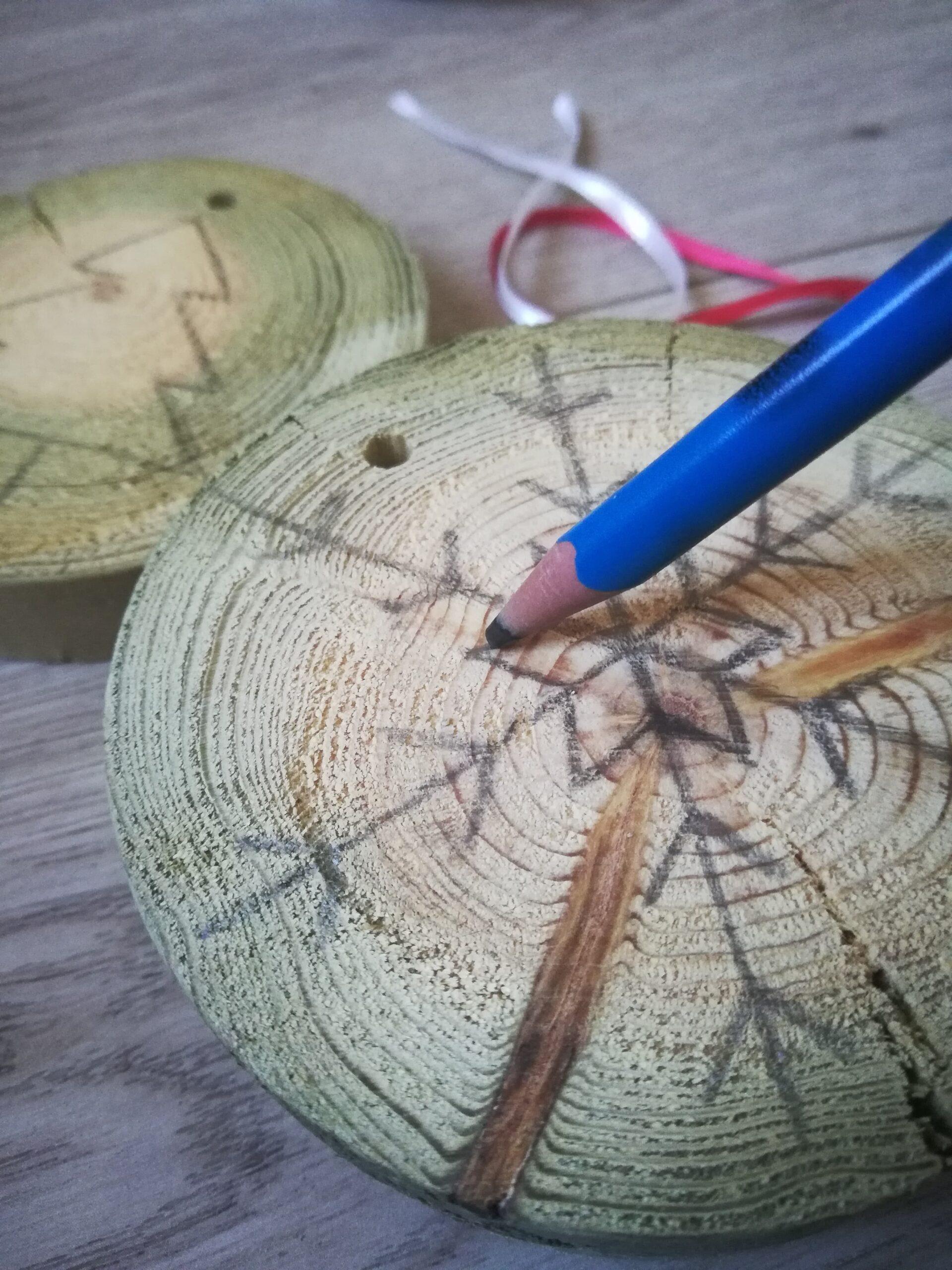 Sur une rondelle de bois, un flocon de neige se dessine. Un crayon de papier a sa pointe posée sur le bois, quelqu'un que nous ne voyons pas le tient et dessine avec.