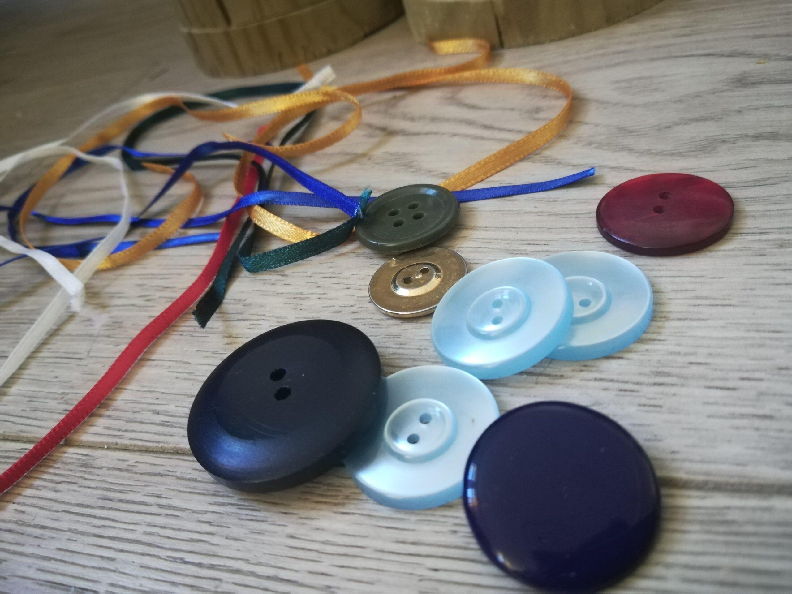 Du matériel récupéré est posé sur le sol. Des fils de toutes les couleurs et des boutons, des gros et des petits, des noirs, des bleus et des dorés.