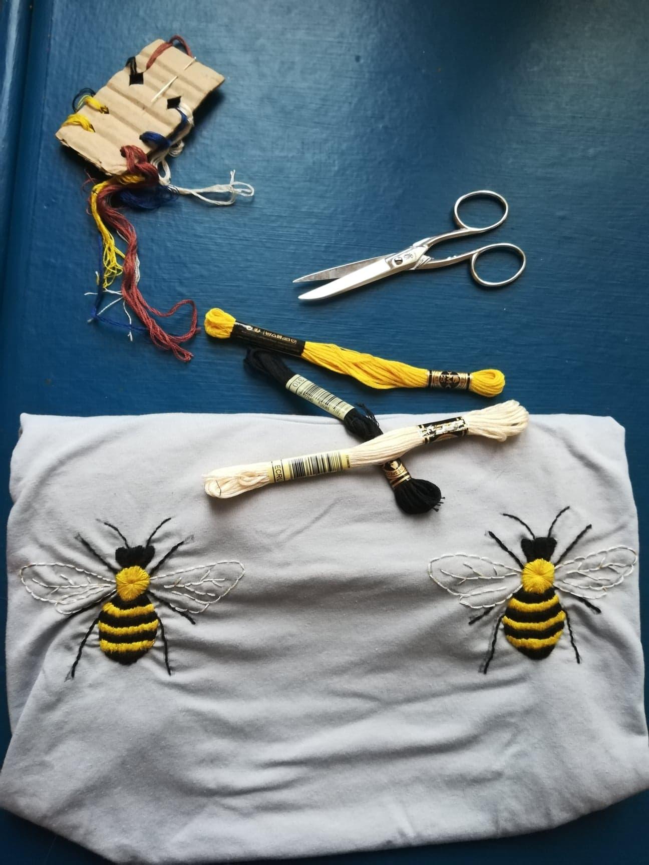 Sur un table un kit de broderie est posé. Une paire de ciseaux, des fils jaunes, blancs et noirs. Deux abeilles sont brodées symétriquement sur un T-shirt mais elles ne sont pas totalement terminées, les ailes sont encore à remplir.