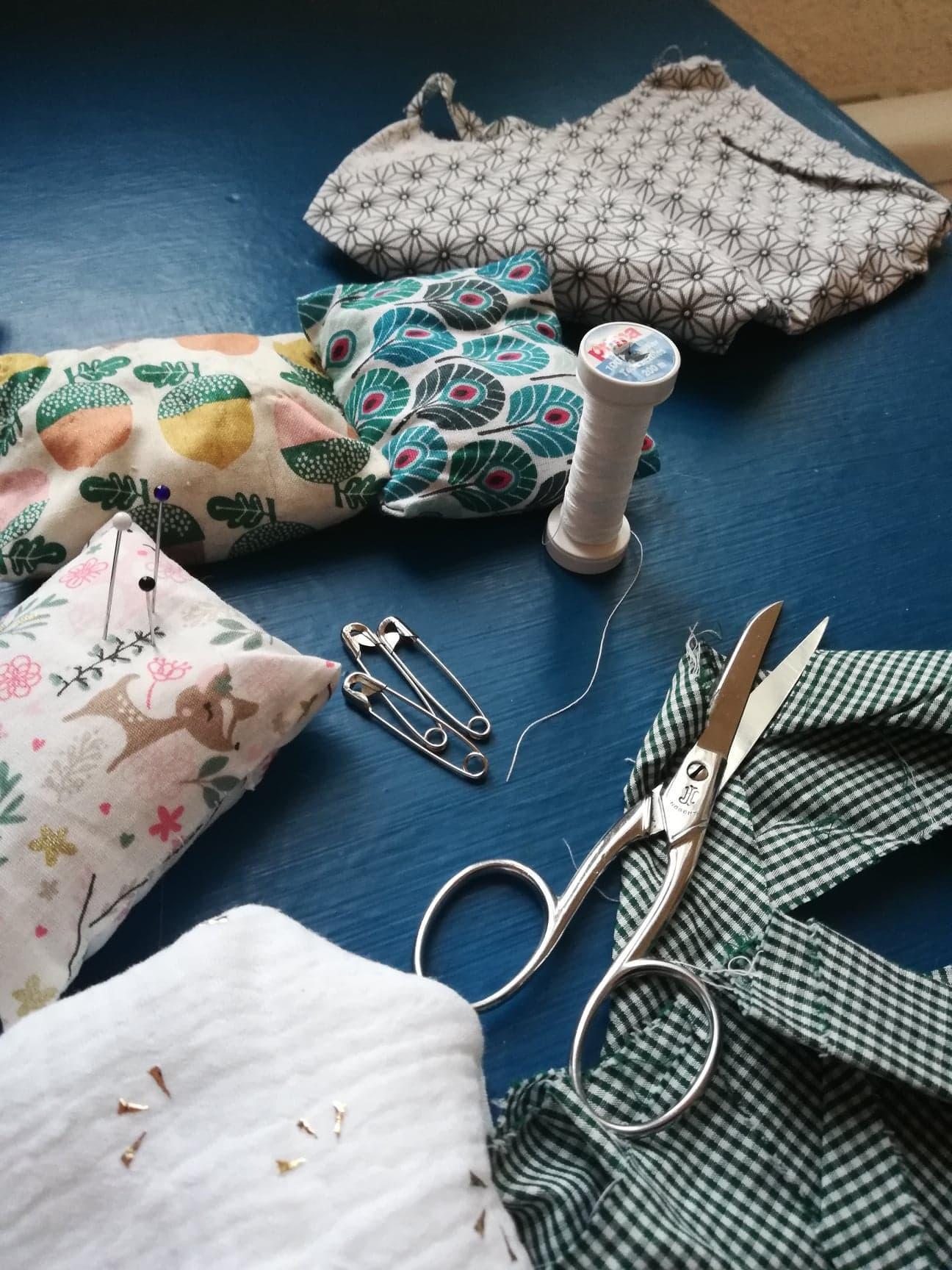 Tout un kit de couture est posé sur une table. Une paire de ciseaux, du fil blanc, des épingles à nourrice et plusieurs tissus colorés et à motifs (des petits cerfs, des carreaux, des glands).