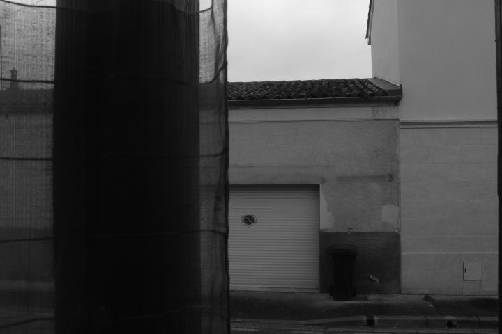 Au premier plan, une fenêtre avec un rideau à demi fermé. A l'arrière plan, une maison de l'autre côté de la rue. L'image est en noir et blanc.