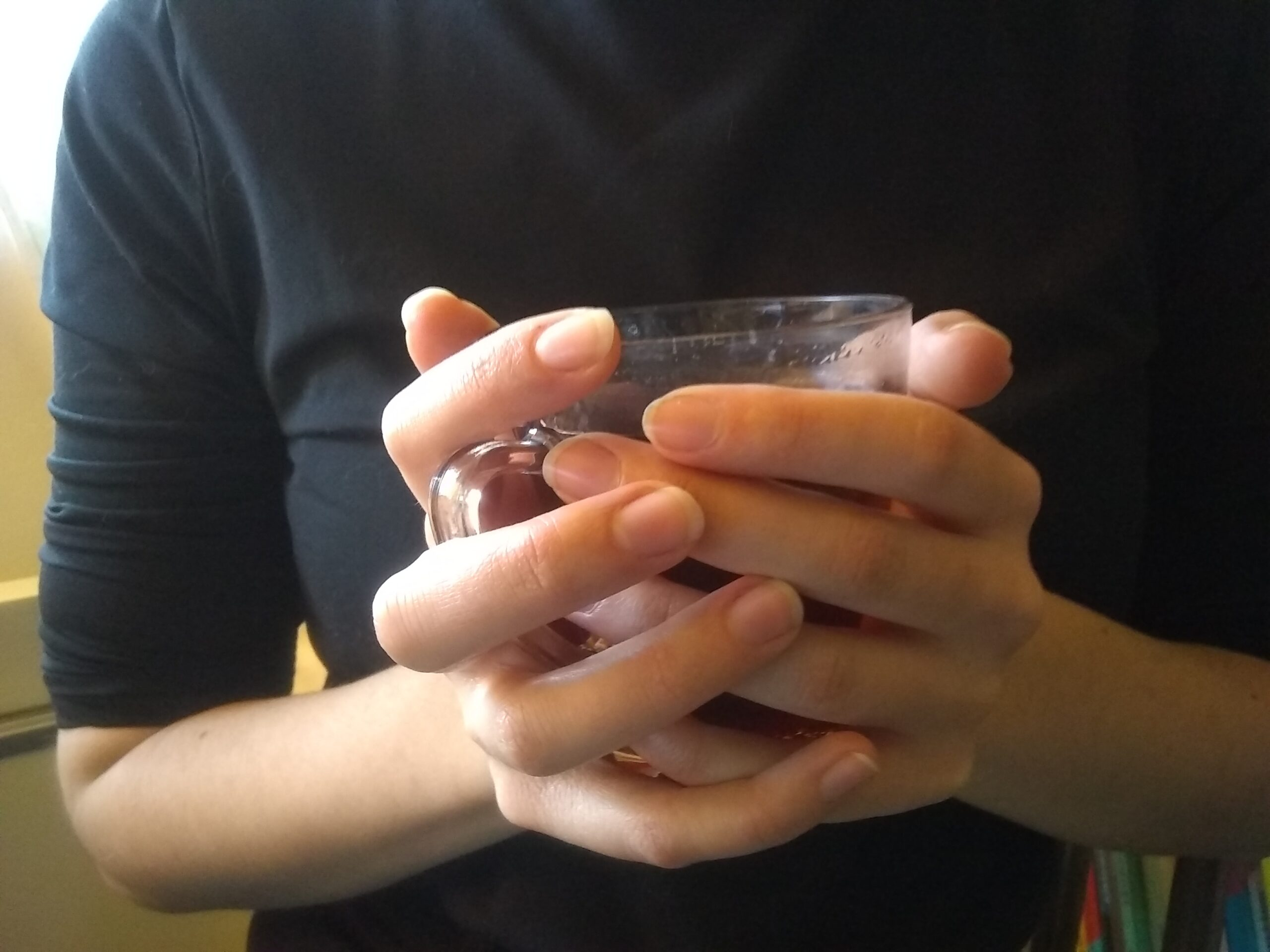 Tasse de thé chaud entre des mains, on voit de la buée sur les parois de la tasse