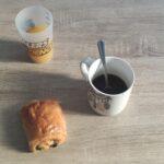 Gros plan sur un petit déjeuner. Il est posé sur une table marron clair. En haut, du jus d'orange, au centre, un café, une cuillère dans une tasse blanche. En bas, une chocolatine.