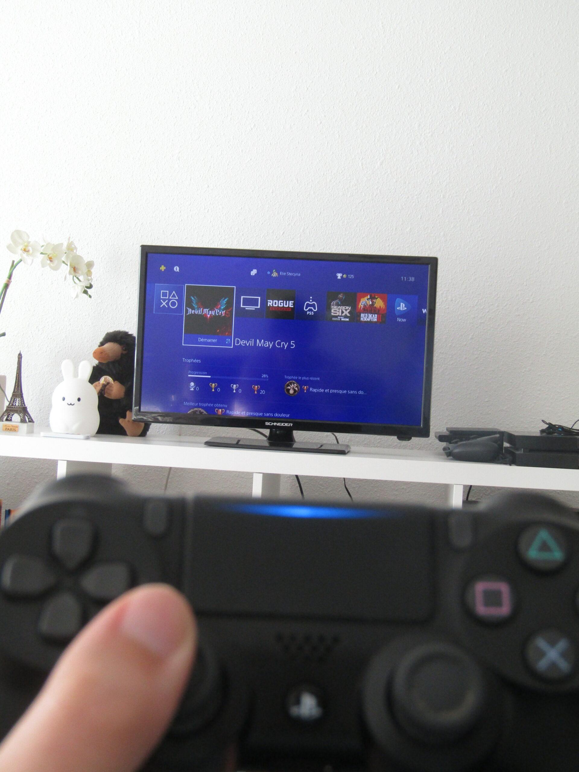 Une télé allumée sur un écran d'accueil de Playstation 4 avec une mannette tenue en main au premier plan