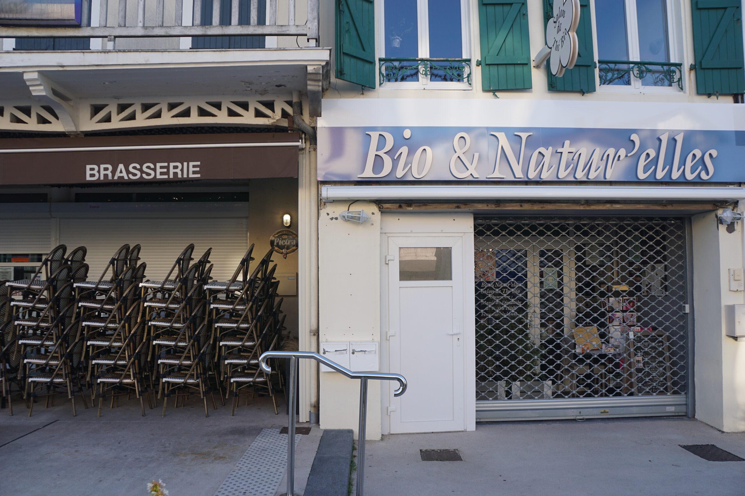 Photographie des devantures d'une boutique et d'un café, fermées.