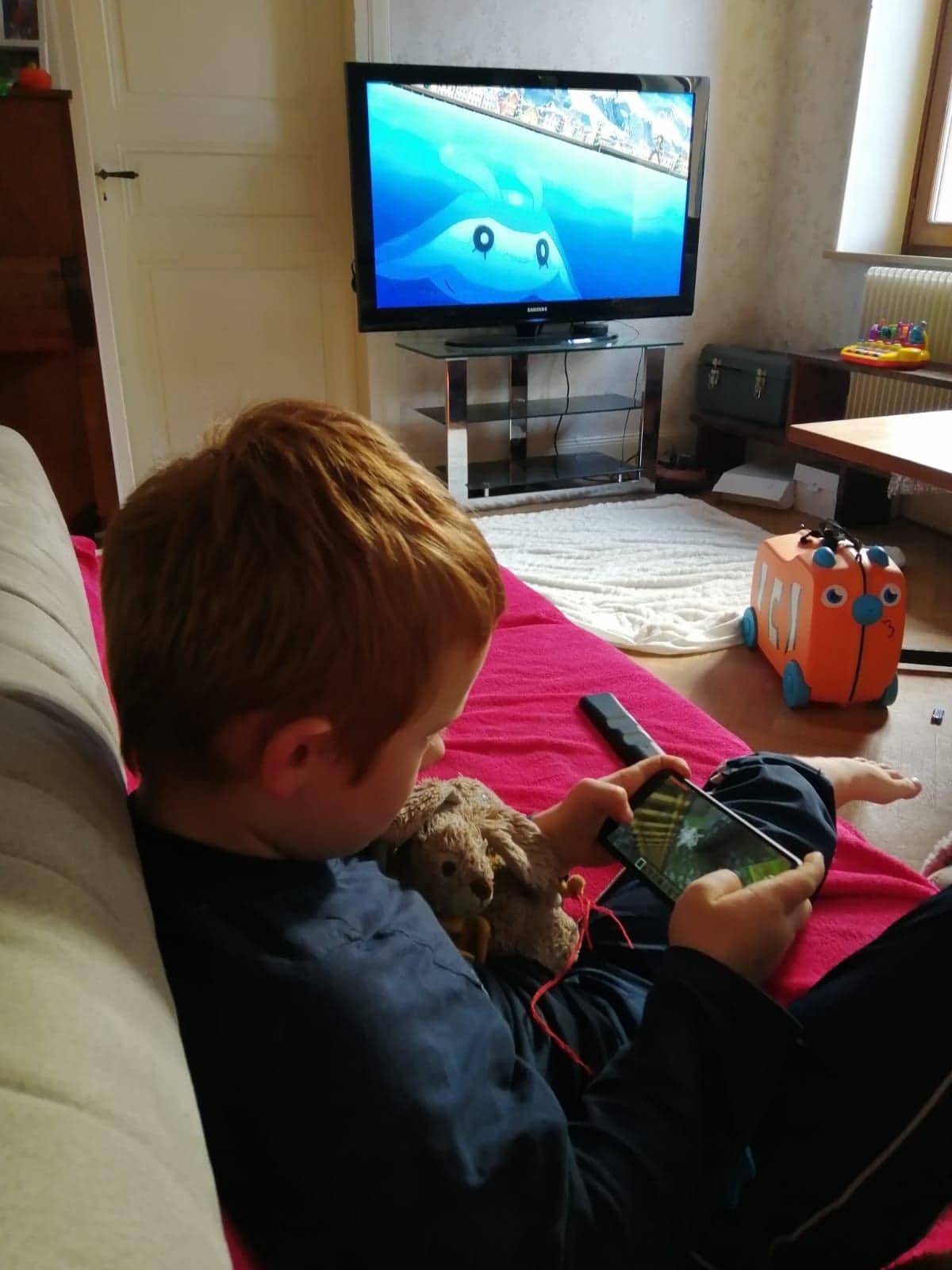 Sur cette photo on peut voir en premier plan, un petit garçon avec son doudou dans les bras, en train de jouer à un jeu d'action sur un téléphone portable. En arrière-plan, la télévision est allumée et joue un film d'animation qui ne semble pas intéresser le garçon.