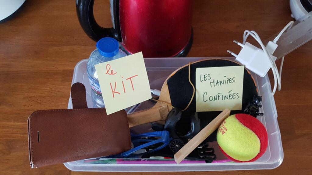 """Le kit contient une raquette de ping pong, une balle, un téléphone portable, une bouteille d'eau, un chargeur, une webcam et d'autres objets. On voit également une bouilloire sur le côté. Deux posti-it indiquent """"le Kit"""" et """"Les manipes confinées"""""""