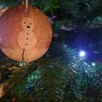 Entre les branches du sapin, une décoration faite main. Un bonhomme de neige peint sur une rondelle de bois.