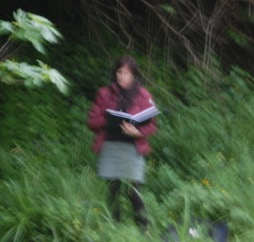 Photo de l'artiste Deborah Bowman pendant une intervention pédagogique, un cahier à la main, se tenant debout au milieu de la végétation verdoyante.