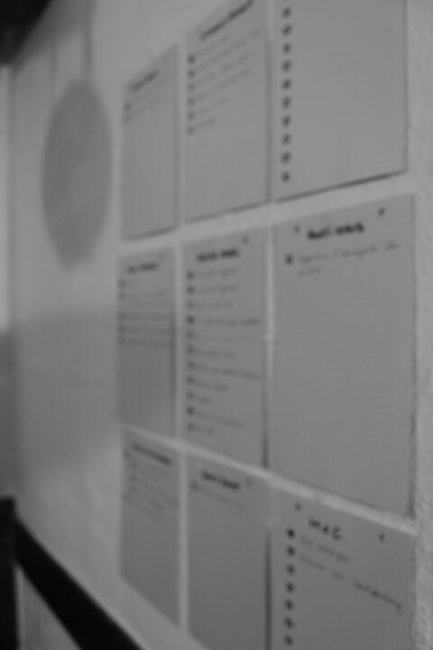 Des fiches bristol accrochées sur un mur claire. Elles semble remplies d'informations, comme des listes à puce. L'image est en noir et blanc.