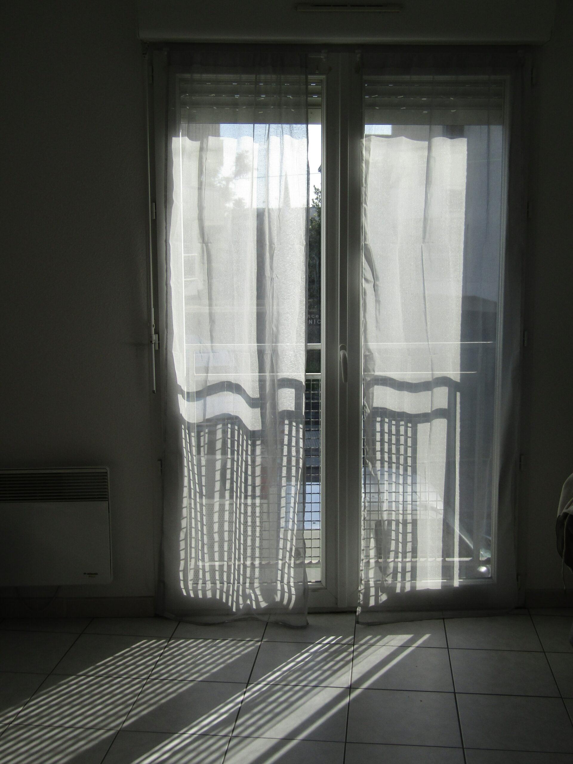 Une fenêtre fermée qui laisse entrer la lumière. Il y a des longs rideaux devant cette fenêtre.