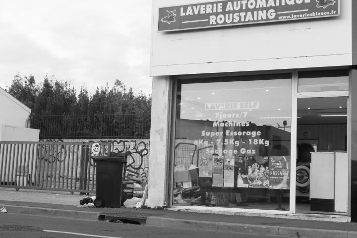 """L'extérieur d'une laverie. Un panneau sur le haut du bâtiment indique """"Laverie automatique roustaing"""". Sur la gauche de l'image il y a des poubelles ou une décharge, juste à coté de la laverie. L'image est en noir et blanc."""